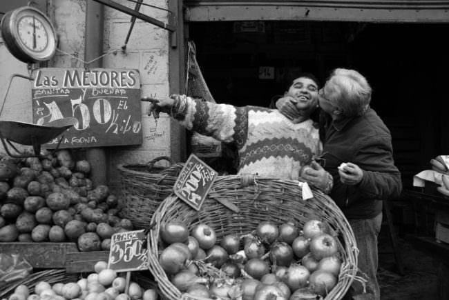 Ein Mann an einem Obststand wird auf die Wange geküsst