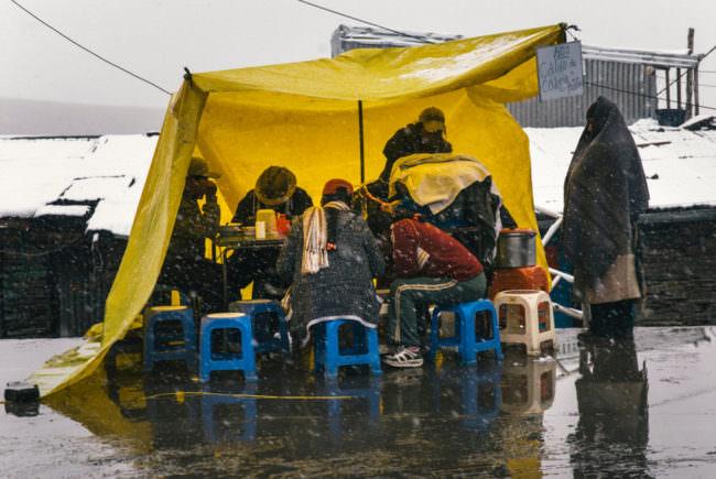 Menschen unter einer gelben Plane