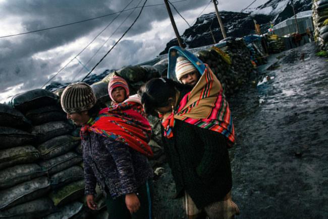 Frauen tragen ihre Kinder mit Tüchern