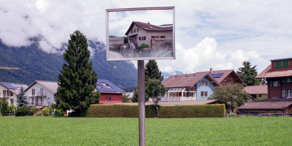 Ansicht einer Ortschaft mit einem Sichtspiegel der verzerrt ein Haus abbildet.