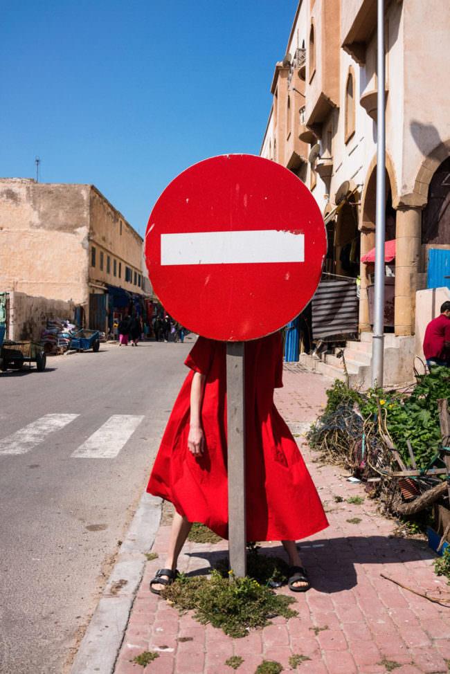Eine Frau hinter einem roten Verkehrsschild
