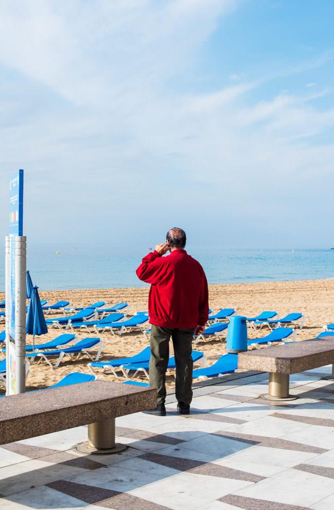 Ein Mann mit roter Jacke vor blauen Liegen