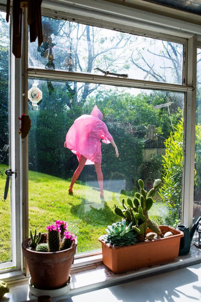 Eine Frau mit pinker Regenjacke durch ein Fenster