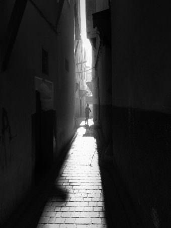Ein Junge läuft zwischen Häuserschluchten.