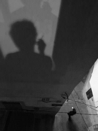 Der Schatten eines rauchenden Menschen an einer Häuserwand.