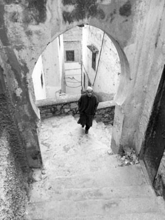 Ein Mann läuft durch einen Torbogen und blickt nach oben.