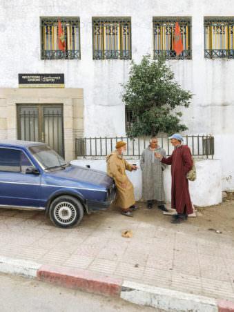 Männer, die vor einem blauen Auto vor einem hellen Haus stehen und sich unterhalten.