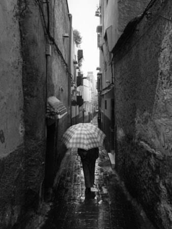 Ein Mensch mit einem Schirm, der durch eine Häuserschlucht läuft.
