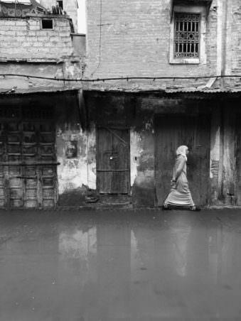 Eine Frau, die entlang einer Häuserwand vor einer großen Pfütze läuft.