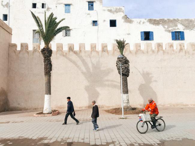 Menschen auf einem Platz vor einem Sandsteingebäude und Palmen.