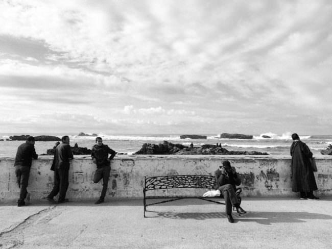 Menschen an einer Promenade am Meer.