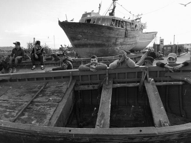 Männer, die an einem Ruderboot lehnen, vor einem alten Schiffswrack.