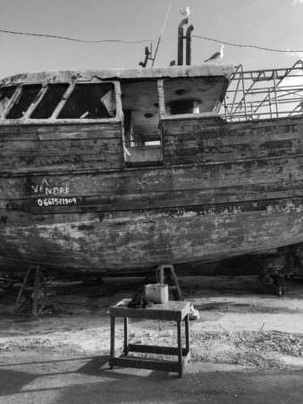 Ein altes Holzschiff, das an Land liegt.
