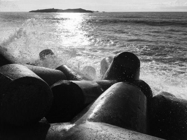 Steine, die am Meer liegen und von Wellen getroffen werden.