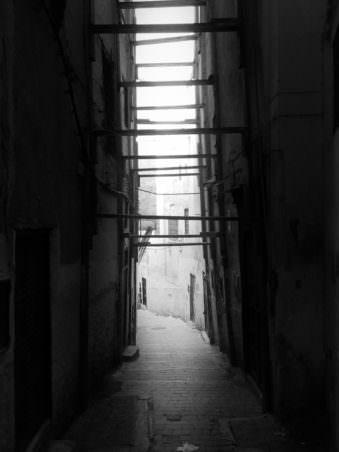 Eine enge Gasse zwischen Häusern in Schwarzweiß.