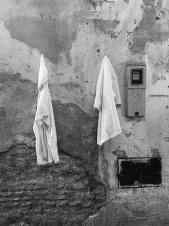 Kleidung, die an einer heruntergekommenen Häuserwand hängt.