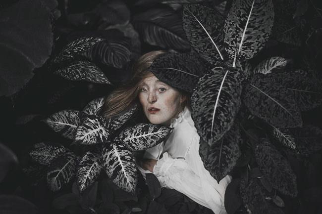 Eine Frau zwischen Blättern