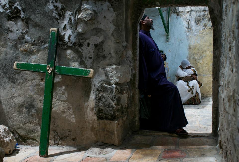 Ein Kreuz steht neben einer Tür, dahinter beten Menschen
