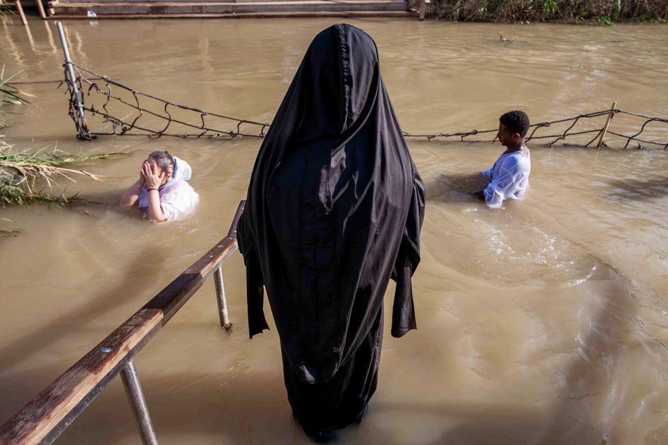 Eine verschleierte Frau sieht einer Taufe zu