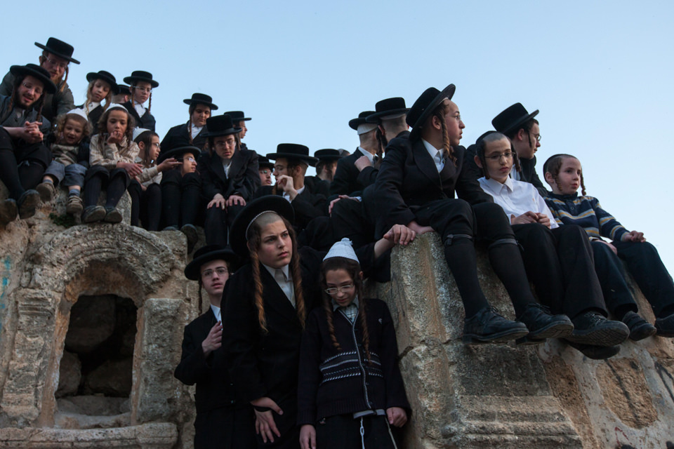 Orthodox-jüdische Kinder sitzen auf einer Mauer
