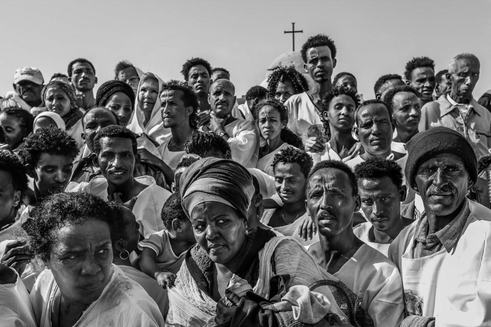 Eine Menschenmenge steht vor einem Kreuz