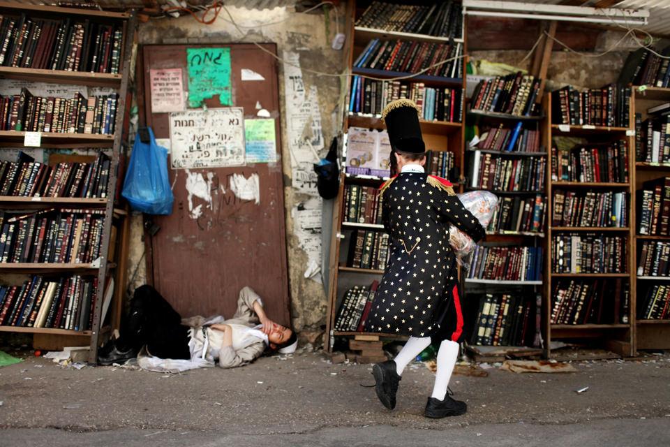 Eine Person liegt am Boden, eine andere geht an ihr vorbei