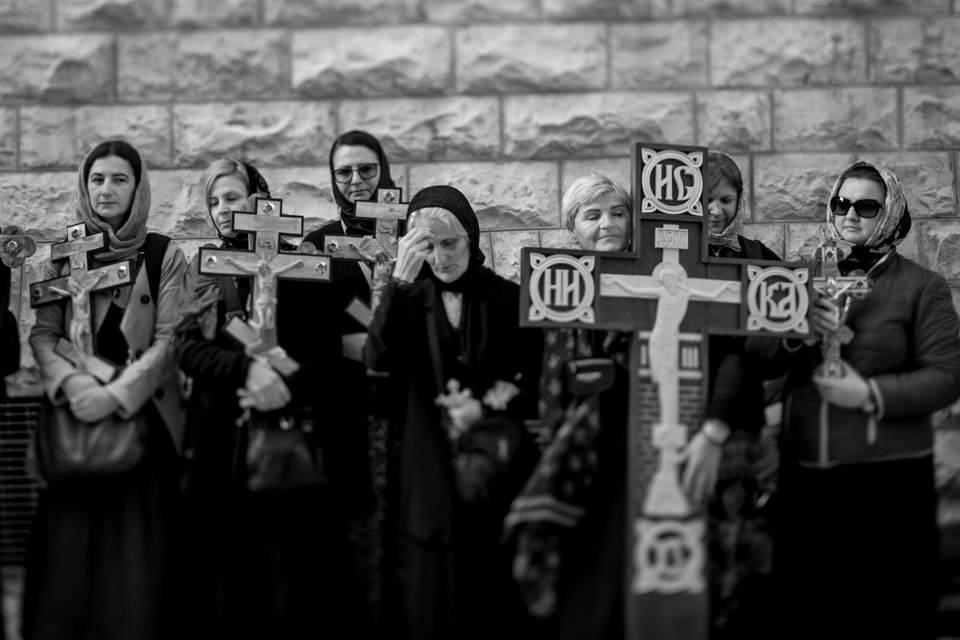 Menschen stehen vor einer Wand und halten hölzerne Kreuze