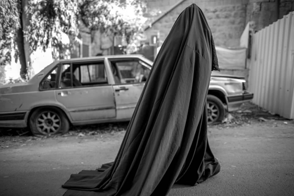 Eine verschleierte Frau geht an einem Auto vorbei