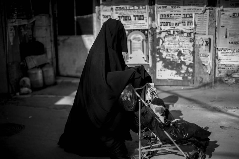 Eine verschleierte Frau schiebt einen Kinderwagen
