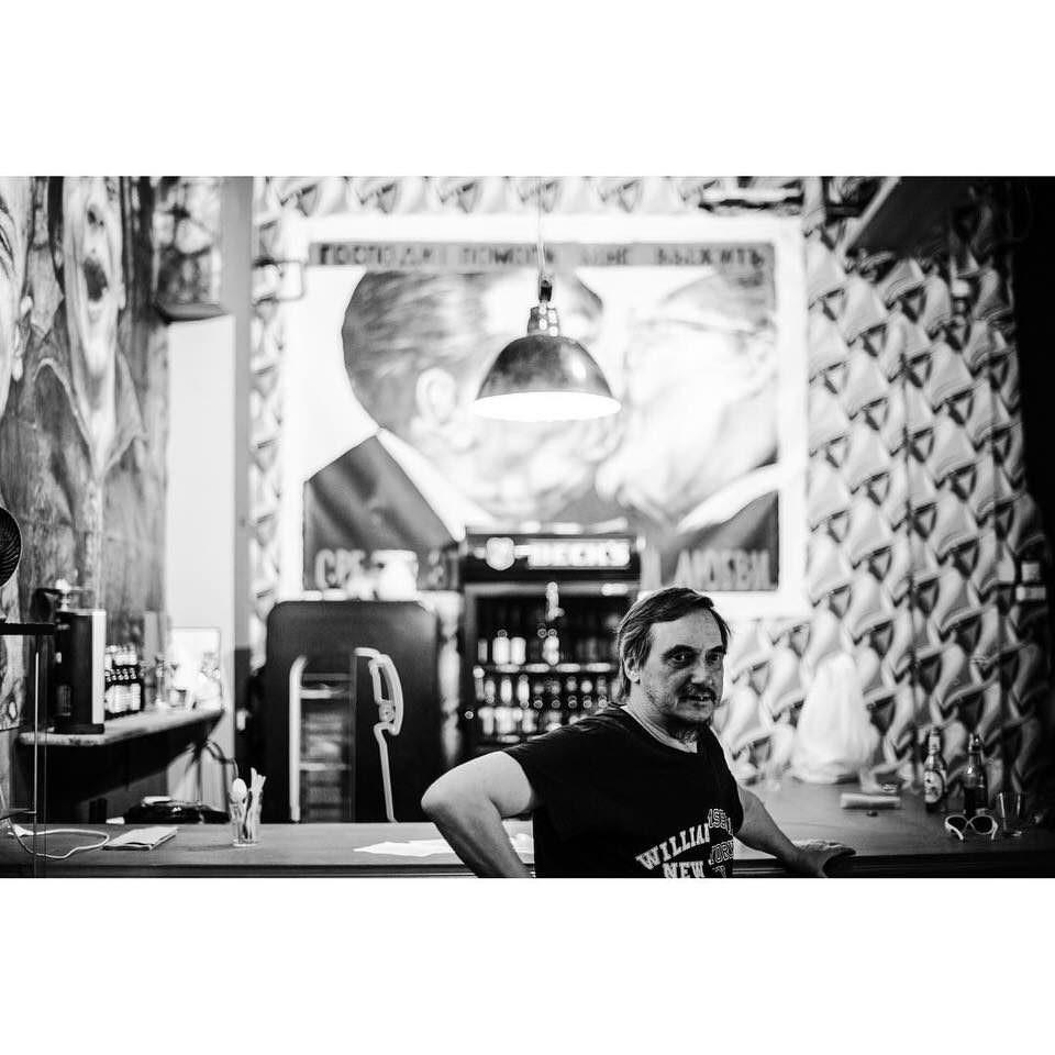 Schwarzweißes Foto einer Person in einem Innenraum in einer Barsituation.