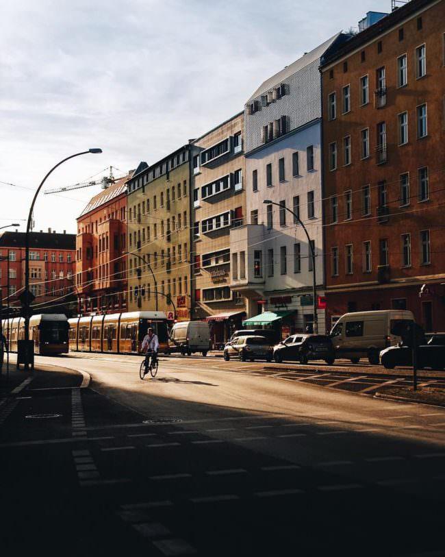 Straßenszene im Sonnenlicht mit bunten Hausfassaden und einer radfahrenden Person.