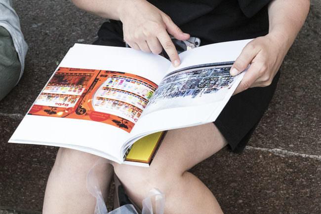 Aufgeschlagenes Buch wird angeschaut und liegt auf dem Schoß einer Person.