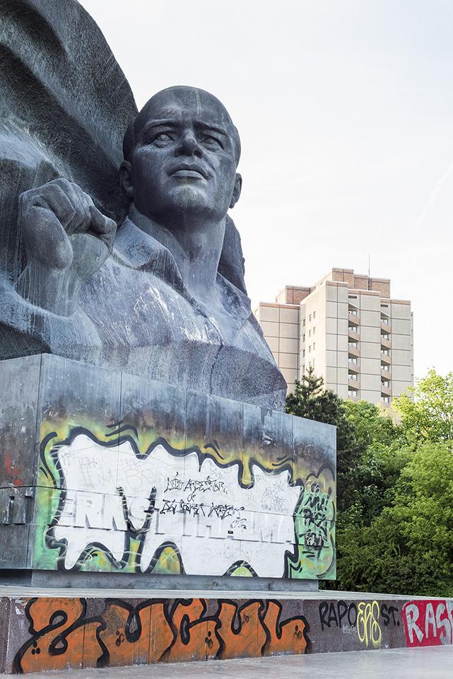 Denkmal Staue im Vordergrund mit Graffiti bemalt, dahinter ein Hochhaus und Grünwuchs.
