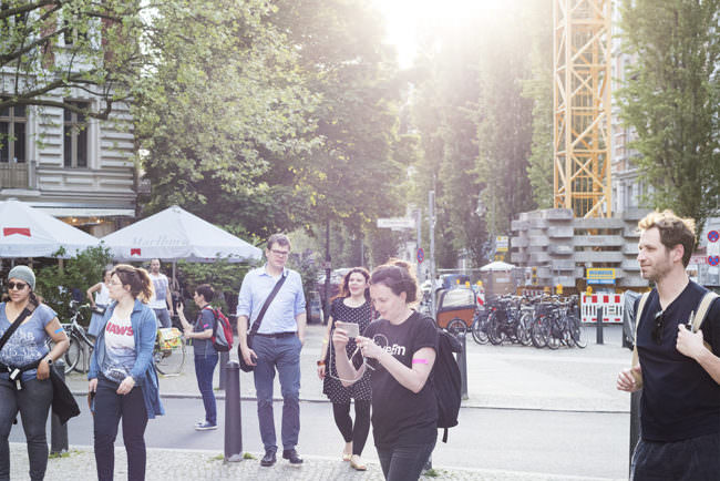 Gruppe von Personen im Sonnenlicht laufend fotografiert in einer Stadtszenerie.