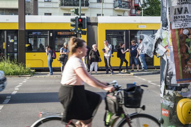 Frau auf einem Fahrrad fährt vorn durchs Bild, im Hintergrund Personen die an einer Ampel warten. Hinten ihnen fährt eine Straßenbahn entlang.