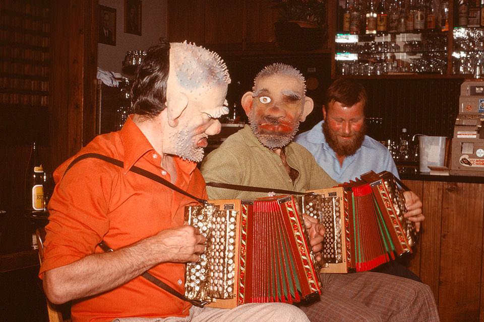 Drei Männer mit Masken spielen Akkordeon