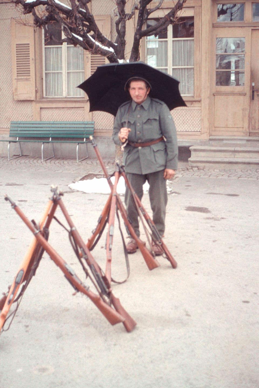 Ein Soldat mit Regenschirm vor Gewehren