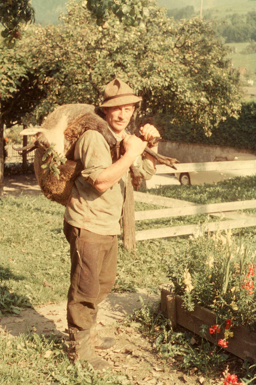 Ein Mann mit Tierleiche über den Schultern