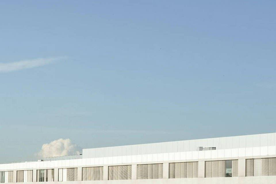 Langes Gebäude und eine Wolke unter einem weiten blauen Himmel.