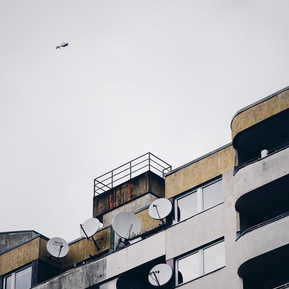 Fassade mit Balkonen, Fenstern und Satellitenschüsseln vor einem grauen Himmel, an dem ein Helikopter schwebt.
