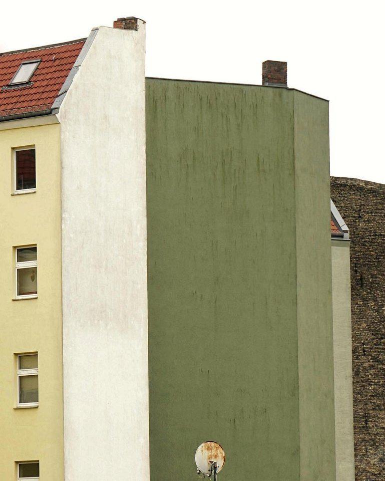 Hausfassaden in Gelb, Grün und Braun, davor eine Satellitenschüssel.