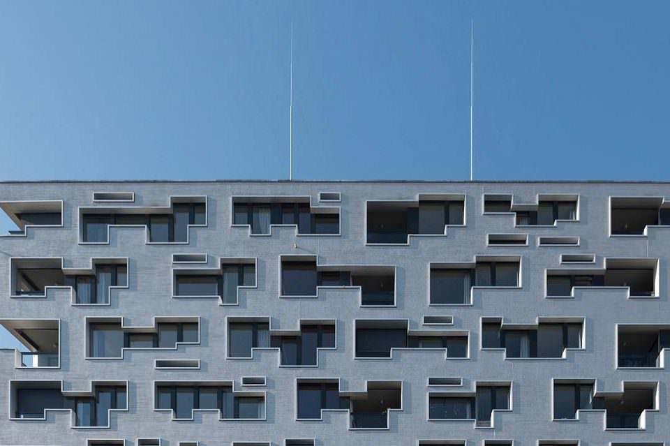 Moderne Fassade mit verwinkelten Fensteröffnungen, auf dem Gebäude zwei lange Antennen, vor einem blauen Himmel.