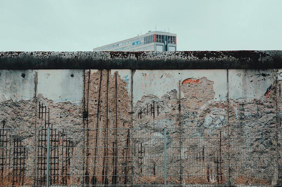 Mauer mit teilweise zerstörter Oberfläche, unter der Steine und Metall sichtbar sind.