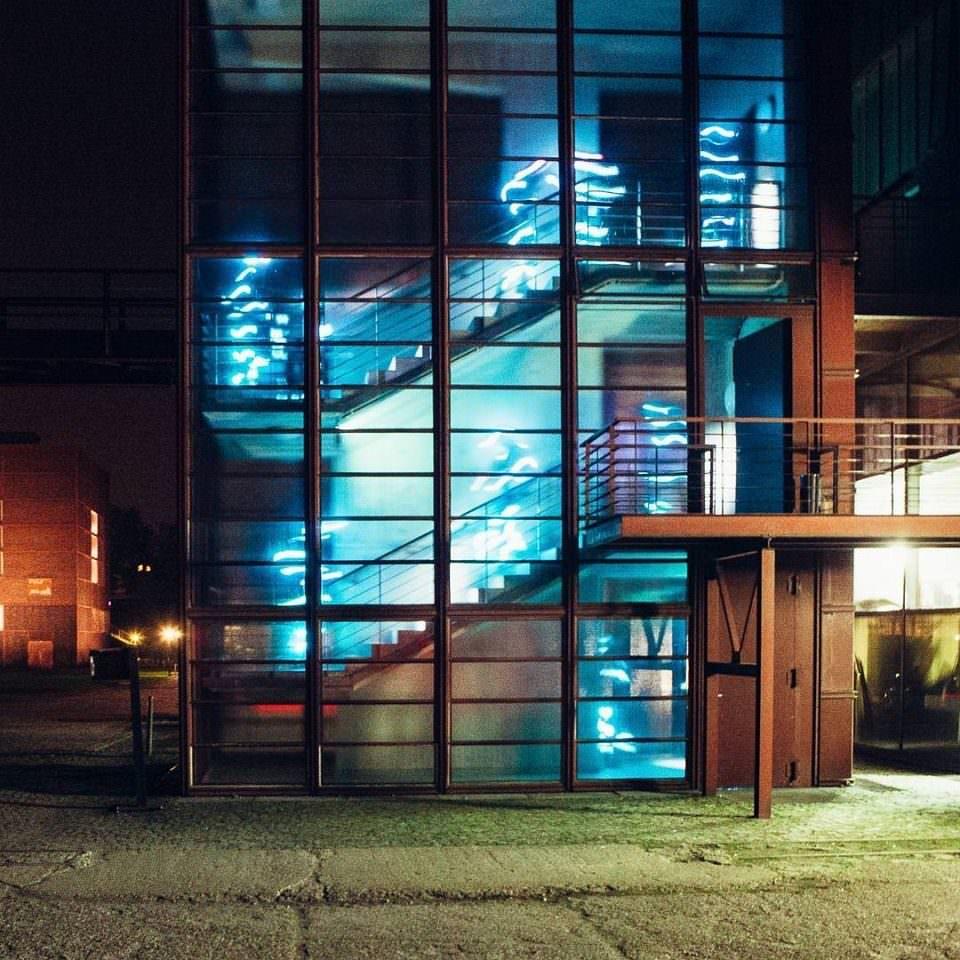 Moderner Glasbau, in der Dunkelheit bunt erleuchtet.
