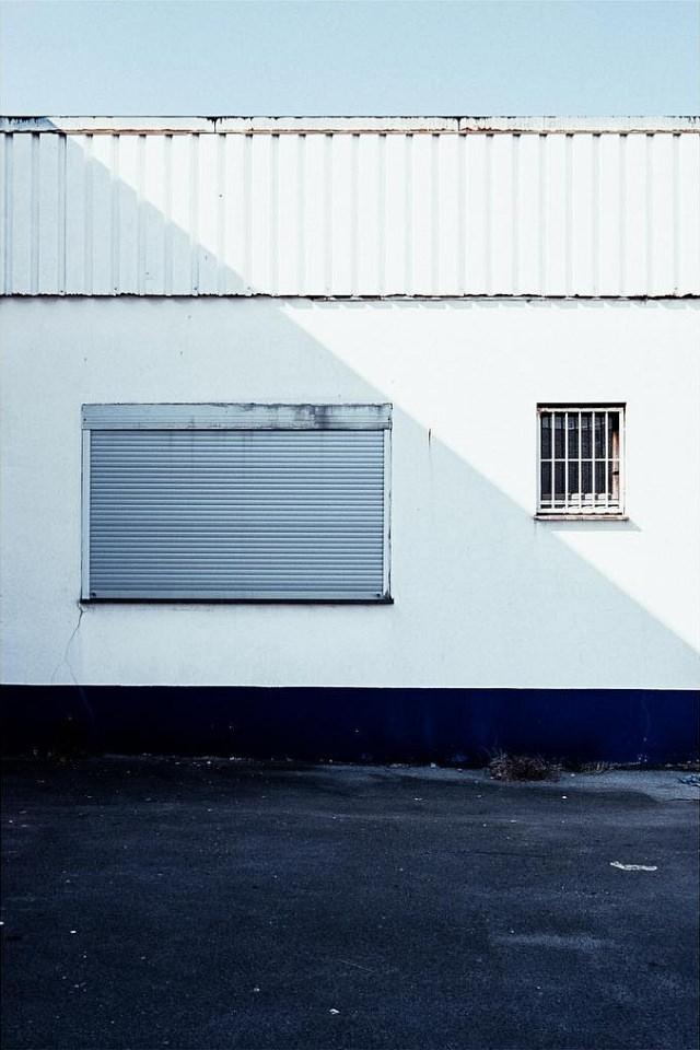 Helle Fassade mit dunkel abgesetztem Sockel und zwei unterschiedlichen Fenstern, auf die diagonal ein Schatten fällt.