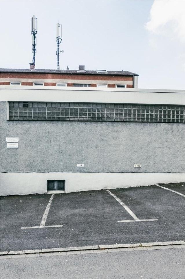 Schräg abfallender Parkplatz an der Rückwand eines grauen Gebäudes.