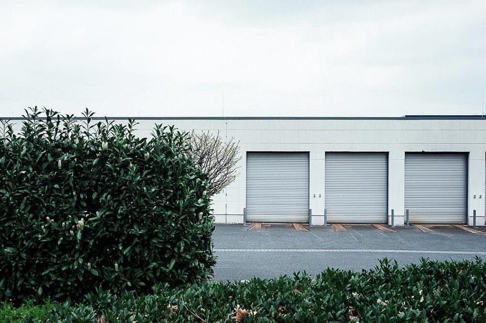 Hecke vor einer Halle mit drei geschlossenen Rolltoren.