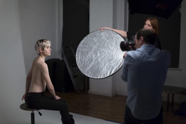 Fotograf fotografiert sitzendes Modell, eine Assistentin hält einen Reflektor.