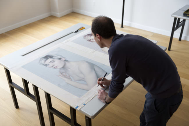 Ein Mann beugt sich über einen Tisch, auf dem zwei Bilder einer Frau liegen.
