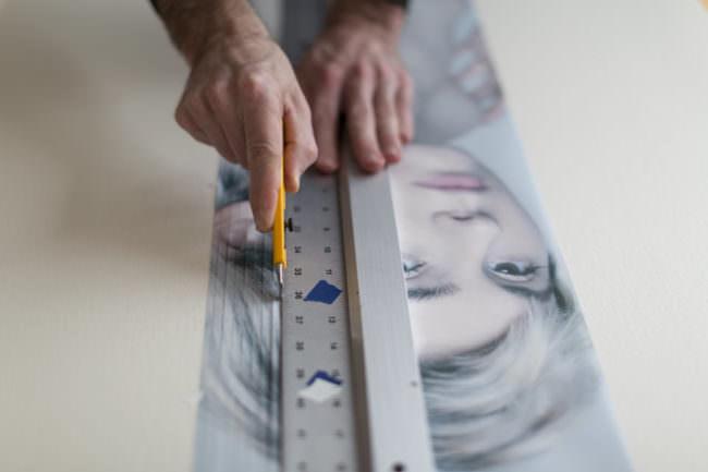 Zwei Hände, die mit einem Lineal und einem Messer das Portrait einer Frau in Streifen schneiden